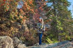 Una ragazza che si siede su una roccia Fotografia Stock