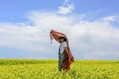 Una ragazza che sta in fiori Fotografie Stock Libere da Diritti