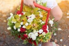 Una ragazza che tiene una bella composizione dei fiori in sue mani fotografia stock