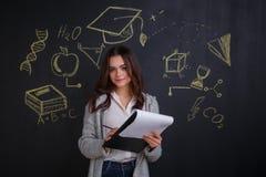 Una ragazza che tiene una cartella nera con le carte, stanti accanto ad una lavagna con un'immagine delle scienze Fotografia Stock Libera da Diritti