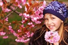 Una ragazza che tiene un ciliegio fiorisce e sorridere immagini stock libere da diritti