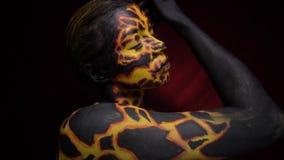 Una ragazza con bodypainting sul suo corpo nell'immagine di lava vulcanica si segna delicatamente alla musica stock footage