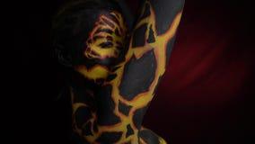 Una ragazza con bodypainting sul suo corpo sotto forma di lava vulcanica, giri affronta in avanti video d archivio