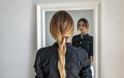 Una ragazza con capelli biondi lunghi intrecciati in una treccia sta stando all'interno di fronte allo specchio fotografie stock libere da diritti