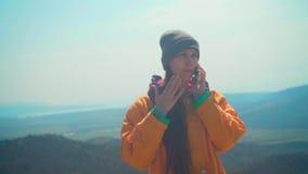 Una ragazza con capelli lunghi in rivestimento giallo, cappuccio grigio e vetri sta stando sulla montagna e sta parlando sul tele video d archivio