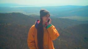 Una ragazza con capelli lunghi in rivestimento giallo, cappuccio grigio e vetri sta stando sulla montagna e sta parlando sul tele archivi video