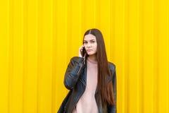 Una ragazza con capelli lunghi scuri, parlanti sul suo telefono cellulare Su una priorità bassa gialla Immagine Stock