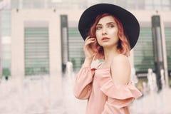 Una ragazza con capelli ricci rosa luminosi e un cappello nero della spiaggia sta sui precedenti della fontana Una ragazza con un fotografia stock