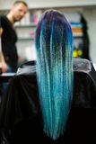 Una ragazza con capelli tinti che si siedono in una sedia allo studio del salone di bellezza Lavoro sopra la dimostrazione Immagini Stock