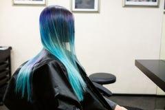 Una ragazza con capelli tinti che si siedono in una sedia allo studio del salone di bellezza Lavoro sopra la dimostrazione Immagine Stock