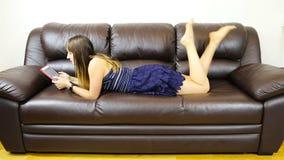 Una ragazza con una compressa sta trovandosi sul suo stomaco su un sofà di cuoio e sta ondeggiando le sue gambe video d archivio