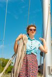 Una ragazza con una corda sulla piattaforma di un yacht guarda intorno e tiene i tronchi sulla sua spalla immagini stock