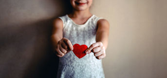 Una ragazza con cuore rosso in sue mani Fotografie Stock Libere da Diritti
