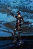 Una ragazza con una figura snella in un vestito fantastico dello specchio con una maschera degli specchi che eseguono nell'arena fotografia stock