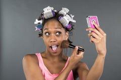 Una ragazza con i bigodini in suoi capelli che esaminano telefono fotografie stock libere da diritti