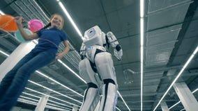 Una ragazza con i palloni che va in giro un cyborg, vista dal basso stock footage