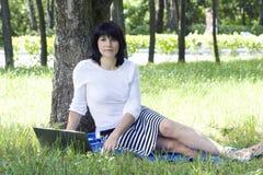 Una ragazza con il computer portatile che si siede in una sosta Fotografia Stock