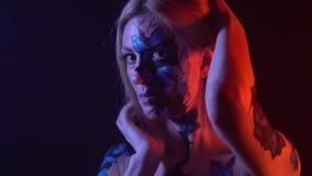 Una ragazza con la vernice di carrozzeria delle farfalle sul suo fronte che segna il suo corpo archivi video
