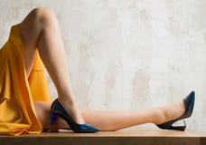 Una ragazza con le gambe nude in scarpe blu fotografie stock