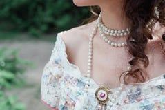 Una ragazza con le perle e le spalle nude fotografia stock