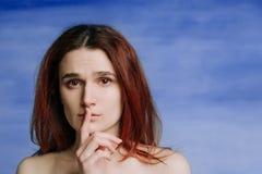 Una ragazza, con le spalle nude ha premuto silenziosamente il suo dito alle sue labbra nel gesto fotografia stock