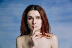 Una ragazza, con le spalle nude ha premuto silenziosamente il suo dito alle sue labbra nel gesto Una persona esprime l'ansia fotografia stock libera da diritti
