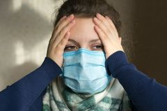 Una ragazza con una maschera medica sul suo fronte tiene la sua testa fotografia stock