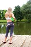 Una ragazza con una stuoia di yoga sta con lei di nuovo alla macchina fotografica fotografie stock