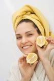 Una ragazza con un asciugamano sulla sua testa tiene due metà di un limone fotografie stock