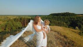 Una ragazza con un bambino nelle sue armi è vestita come gli angeli video d archivio