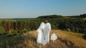 Una ragazza con un bambino vestito come gli angeli camminano in natura video d archivio