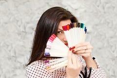 Una ragazza con un bello manicure, tenendo i campioni del manicure, coprenti il suo fronte Brunette immagine stock