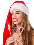 Una ragazza con un bello sorriso tiene le lecca-lecca su un fondo isolato bianco Fotografia Stock