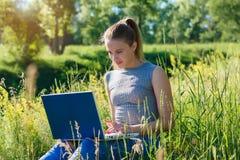 Una ragazza con un computer portatile in natura fra l'erba verde fotografia stock libera da diritti
