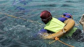 Una ragazza con un giubbotto di salvataggio e un nuoto Fotografie Stock Libere da Diritti