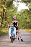 Una ragazza con un motorino su una strada campestre fotografie stock