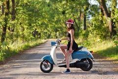 Una ragazza con un motorino su una strada campestre fotografia stock