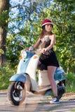Una ragazza con un motorino su una strada campestre immagine stock