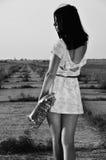 Una ragazza con un sassofono in sue mani sulla terra fotografia stock libera da diritti