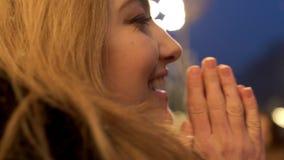 Una ragazza con un sorriso affascinante sta soffiando le sue palme Primo piano video d archivio