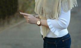 Una ragazza con un telefono in sue mani fotografia stock