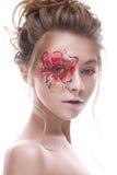 Una ragazza con un trucco creativo sotto forma di fiore dell'rosso-oro sul suo occhio Bello modello nell'immagine di un fiore del fotografia stock