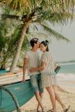 Una ragazza con un uomo che tiene una barca vicino all'oceano Fotografie Stock Libere da Diritti
