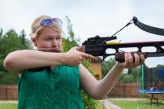 Una ragazza con una balestra che punta su un obiettivo Fotografie Stock