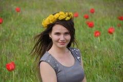 Una ragazza con una corona dei denti di leone su lei capa Bella ragazza leggiadramente in un campo fra i fiori dei tulipani Fotografie Stock Libere da Diritti