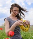 Una ragazza con una corona dei denti di leone in sue mani Campo dei tulipani Fotografia Stock