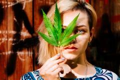 Una ragazza con una foglia della cannabis vicino al suo fronte Fotografie Stock