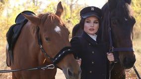 Una ragazza conduce due bei cavalli dietro le redini nei raggi del sole di autunno video d archivio