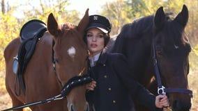 Una ragazza conduce due bei cavalli dietro le redini nei raggi del sole di autunno archivi video