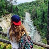 Una ragazza controlla un fiume della montagna Immagine Stock Libera da Diritti